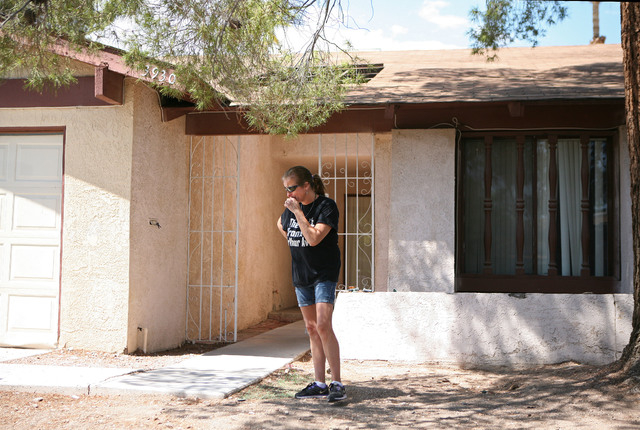 Julie Ramos is overcome with emotion while standing outside her home before talking to the media during a news conference on Autumn Street Wednesday, July 30, 2104, in Las Vegas. The Ramos family  ...