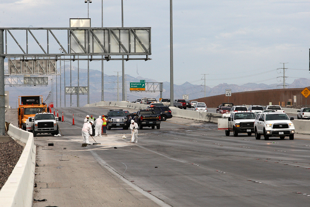 Workers cleanup debris after a jackknifed semitrailer shut down a portion of the eastbound 215 Beltway Tuesday morning. July 15, 2014 (Michael Quine/Las Vegas Review-Journal)