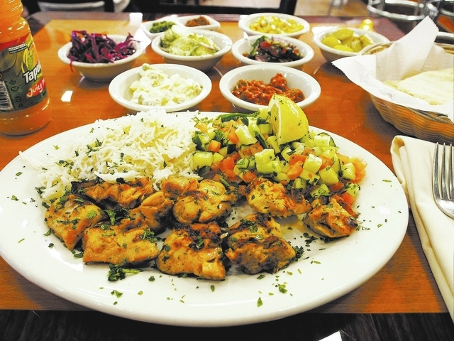 A plate containing grilled chicken, rice and Israeli salad (cucumber and tomato) is seen at the Jerusalem Grill in Las Vegas, Friday, April 26, 2013. Accompanying the dish is; bottom row, Israeli  ...