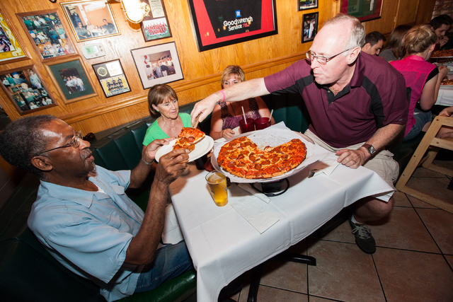 Pete Skubish, right, serves a slice of pizza to Sherman Conley as Shirley Mrozik, second from left, and Lynn Skubish look on at Johnny Mac's, 842 S. Boulder Highway, in Henderson on Saturday, July ...