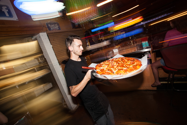 Manager Lucas McGinty brings out a pizza at Johnny Mac's, 842 S. Boulder Highway, in Henderson on Saturday, July 5, 2014. (Chase Stevens/Las Vegas Review-Journal)
