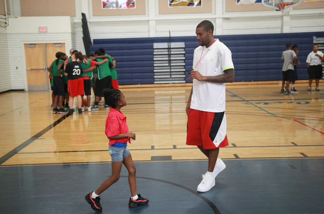 Indiana Pacers guard C.J. Watson talks with Princess Newman, 6, during the Hoops for Hope basketball camp, held by the Quiet Storm Foundation at Doolittle Community Center, 1950 J Street, in Las V ...