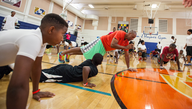 Former NBA player Jerome Williams, center, leads children in push-ups  during the Hoops for Hope basketball camp, held by the Quiet Storm Foundation at Doolittle Community Center, 1950 J Street, i ...