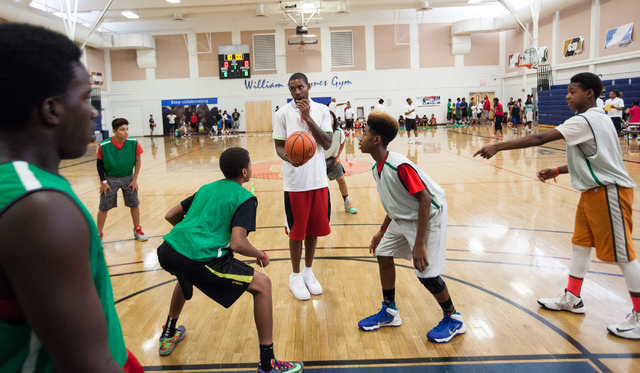 Indiana Pacers guard C.J. Watson, center, prepares to throw a jump ball during the Hoops for Hope basketball camp, held by the Quiet Storm Foundation at Doolittle Community Center, 1950 J Street,  ...