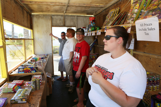 John Grote, from left, Gareth Mitchell, Ryan Leonard and Kim Bjerke wait for customers at the Las Vegas Wranglers Super Rooter Club fireworks stand near the intersection of Tropicana Avenue and Fo ...
