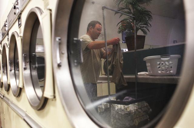 James Shelton folds his clothes at the Wash N Fun Laundromat in Las Vegas on Tuesday, July 15, 2014. (Jason Bean/Las Vegas Review-Journal)