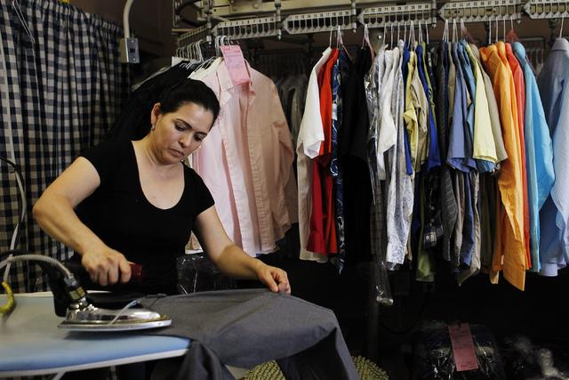 Employee Laura Villalobos irons a customer's pants while working at the Wash N Fun Laundromat in Las Vegas on Tuesday, July 15, 2014.(Jason Bean/Las Vegas Review-Journal)