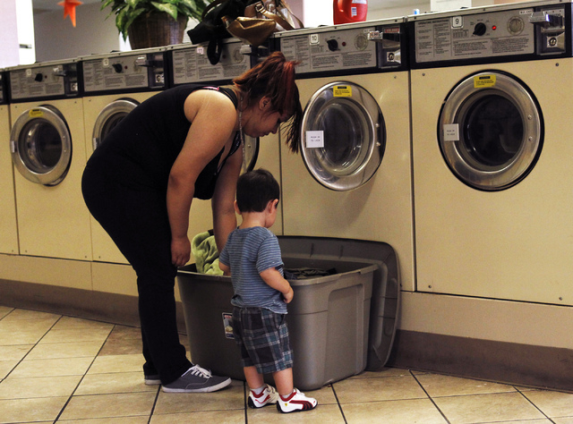 One-year-old Alex Depaz offers to help his mom Daisy Depaz with her clothes while at the Wash N Fun Laundromat in Las Vegas on Tuesday, July 15, 2014.(Jason Bean/Las Vegas Review-Journal)