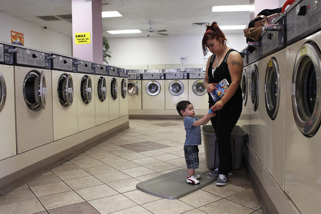 Mom Daisy Depaz offers her 1-year-old son Alex with a toy while doing the family's laundry at the Wash N Fun Laundromat in Las Vegas on Tuesday, July 15, 2014.(Jason Bean/Las Vegas Review-Journal)
