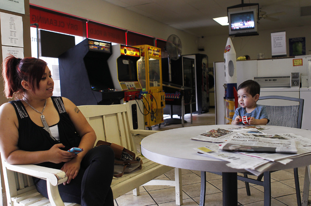 Mom Daisy Depaz uses her smart phone as her son Alex plays with a toy while waiting for the washing machine cycle to end at the Wash N Fun Laundromat in Las Vegas on Tuesday, July 15, 2014.(Jason  ...
