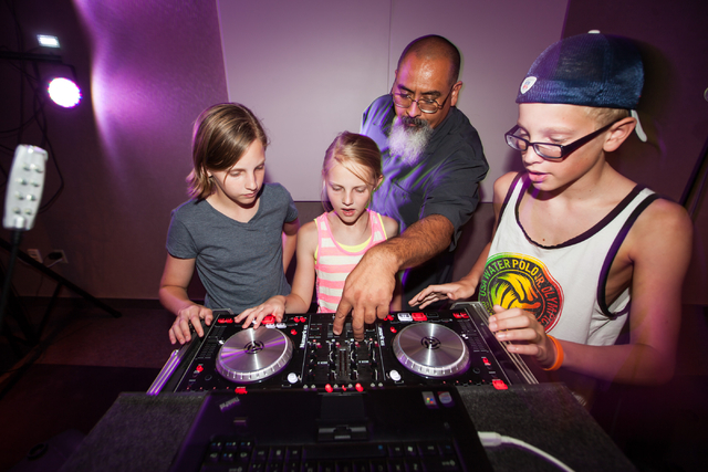 Branch Manager Salvador Avila, third from left, shows Isabel Perham, left, with siblings Gracie, 10, and Ryan, 12, the functions of the DJ controller during a Learn to DJ class at Enterprise Libra ...