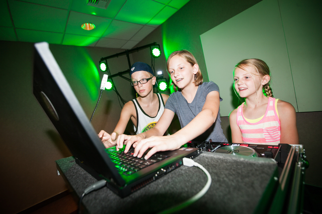 Twelve-year-old Isabel Perham, center, searches for a song to play as siblings Ryan, 12, and Gracie, 10, look on during a Learn to DJ class at Enterprise Library, 25 E. Shelbourne Ave., in Las Veg ...
