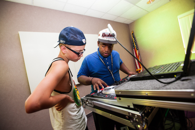 Twelve-year-old Ryan Perham, left, looks on as Darrell Thrasher shows the functions of the DJ controller during a Learn to DJ class at Enterprise Library, 25 E. Shelbourne Ave., in Las Vegas on Th ...