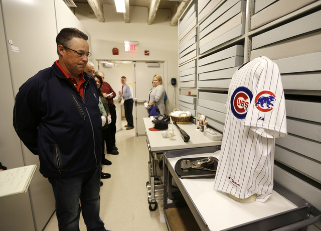 Former Atlanta Braves and Chicago Cubs pitcher Greg Maddux looks the jersey he wore for his 3,000th strikeout during his orientation visit at the Baseball Hall of Fame on Monday, March 24, 2014, i ...