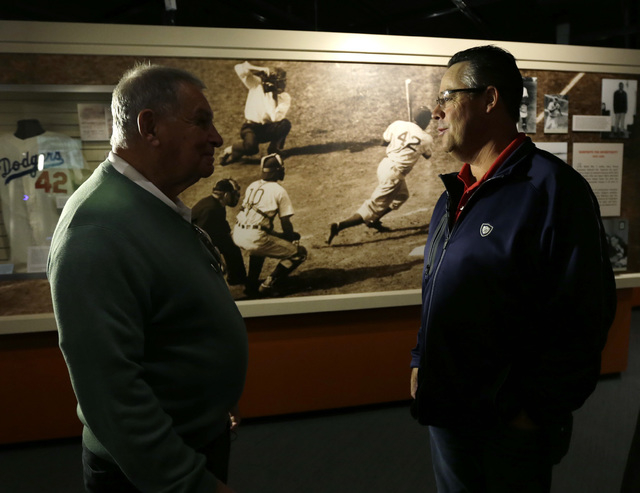 Former Atlanta Braves manager Bobby Cox, left, and former pitcher Greg Maddux visit a Jackie Robinson exhibit during their orientation visit at the Baseball Hall of Fame on Monday, March 24, 2014, ...