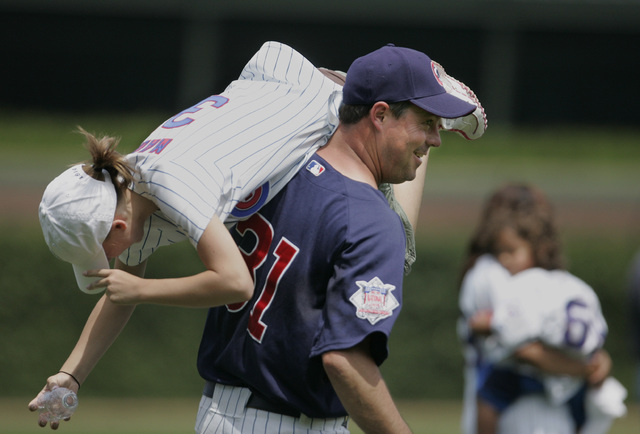 Chicago Cubs piitcher Greg Maddux plays with his daugher Paige during Cubs' Family Day before a baseball game against the Detroit Tigers, Saturday, June 17, 2006, in Chicago. (AP Photo/M. Spencer  ...