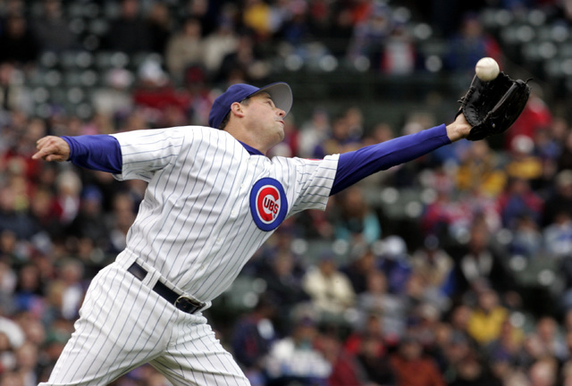 Chicago Cubs pitcher Greg Maddux stretches out to grab a grounder that bounced in the air hit by San Diego Padres' Adrian Gonzalez during the second inning of a baseball game Saturday, May 13, 200 ...