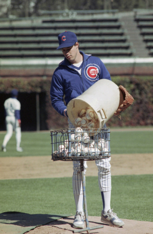 Chicago Cubs starting pitcher Greg Maddux empties a bucket of practice balls into a basket at Wrigley Field as the Cubs get ready for Wednesdays opening game of the National League Championship Se ...