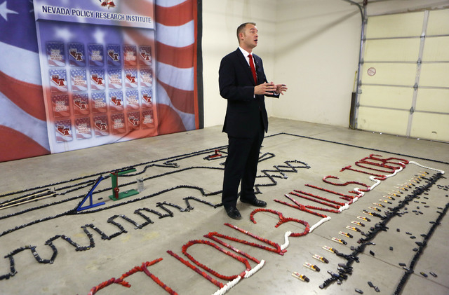 Andy Mathews, president of Nevada Policy Research Institute, stands among a domino demonstration during a news conference at Nevada Policy Research Institute Tuesday, July 22, 2014, in Las Vegas.  ...
