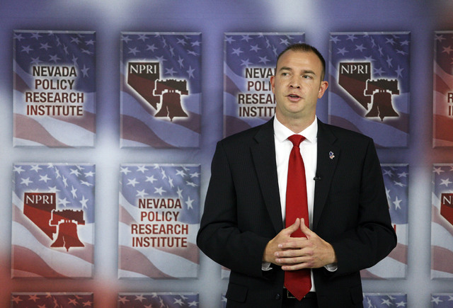Andy Mathews, president of Nevada Policy Research Institute, speaks near a domino demonstration during a news conference at Nevada Policy Research Institute Tuesday, July 22, 2014, in Las Vegas.   ...