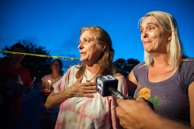 Julie Ramos, left, wife of Richard Ramos who was killed during a home invasion, and a family friend speak to the media during a candlelight vigil Tuesday, July 29, 2014, near where police said a p ...