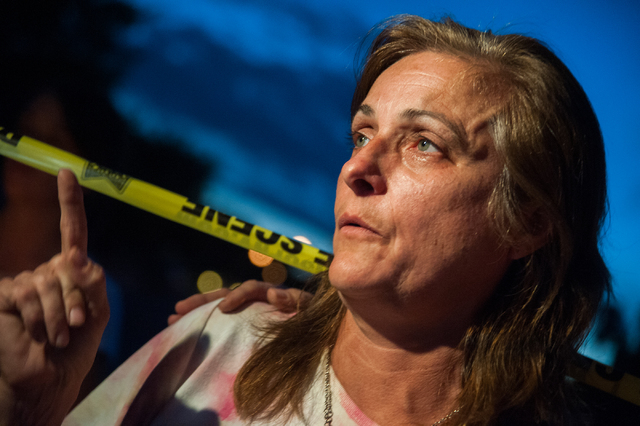 Julie Ramos, wife of Richard Ramos who was killed during a home invasion, speaks to the news media during a candlelight vigil Tuesday, July 29, 2014, near where police said a pair of attackers wen ...