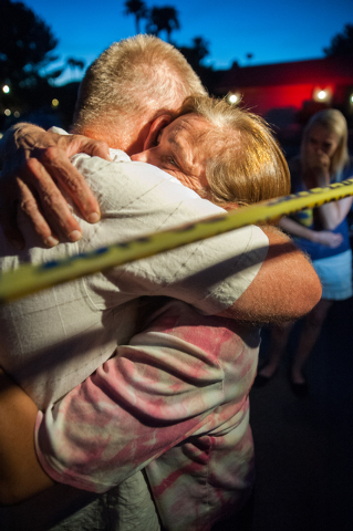 Julie Ramos, wife of Richard Ramos who was killed during a home invasion, right, hugs family friend Mark Todd during a candlelight vigil Tuesday, July 29, 2014, near where police said a pair of at ...