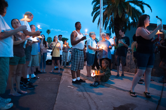 Neighbors and supporters gather during a candlelight vigil Tuesday, July 29, 2014, near where police said a pair of attackers went into a house in the 3900 block Autumn Street earlier Tuesday and  ...