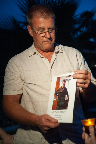 Family friend Mark Todd holds up a photo of the victim Richard Ramos during a candlelight vigil Tuesday, July 29, 2014, near where police said a pair of attackers went into a house in the 3900 blo ...