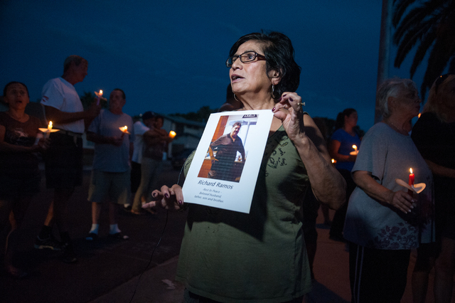A neighbor holds up a photo of the deceased victim Richard Ramos during a candlelight vigil Tuesday, July 29, 2014, near where police said a pair of attackers went into a house in the 3900 block A ...
