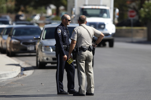 A Nevada Highway Patrol officer, left, and a Las Vegas police officer, communicate at the scene of a home invasion and shooting at the corner of Autumn Street and Rollingwood Drive in Las Vegas Tu ...