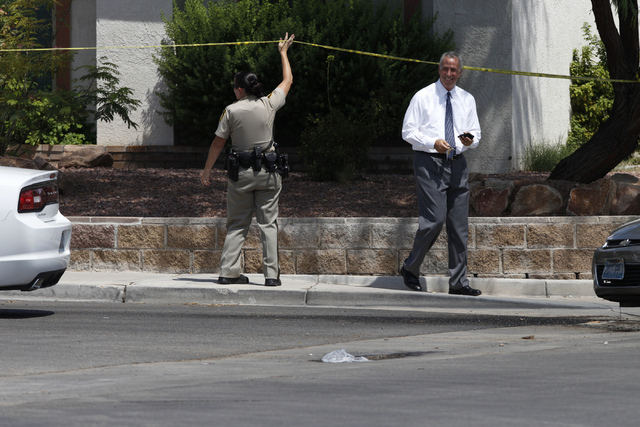 Clark County District Attorney Steve Wolfson, right, leaves the scene of a home invasion and shooting at the corner of Autumn Street and Rollingwood Drive in Las Vegas Tuesday, July 29, 2014. A ho ...