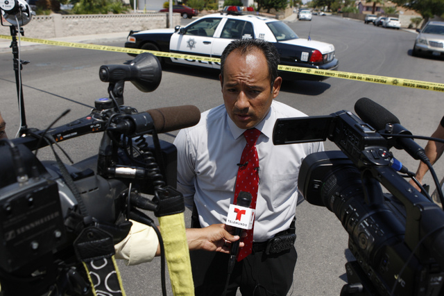 Las Vegas police public information officer Jose Hernandez speaks to the media at the scene of a home invasion and shooting at the corner of Autumn Street and Rollingwood Drive in Las Vegas Tuesda ...