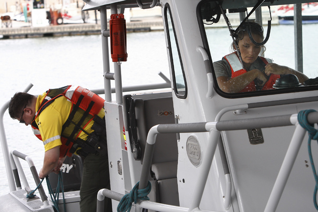 National Park Service rangers Patrick Knierman, left, and Elizabeth Dietzen prepare to head out and search for a missing swimmer at Lake Mead National Recreation Area near Las Vegas on Friday. (Ja ...