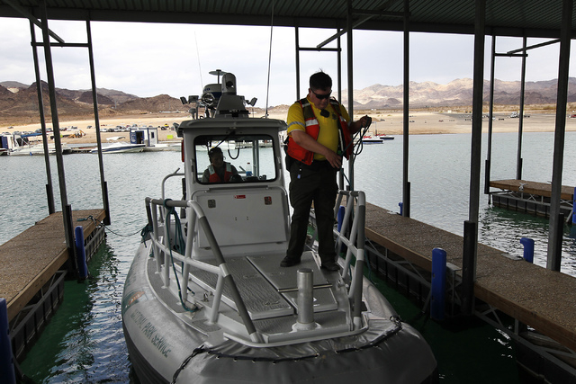 National Park Service rangers Patrick Knierman, right, and Elizabeth Dietzen prepare to head out and search for a missing swimmer at Lake Mead National Recreation Area near Las Vegas on Friday. (J ...