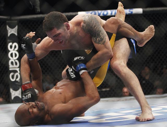 Chris Weidman, top, pounds on Anderson Silva during UFC 168 at the MGM Grand Garden Arena. (Jason Bean/Las Vegas Review-Journal)