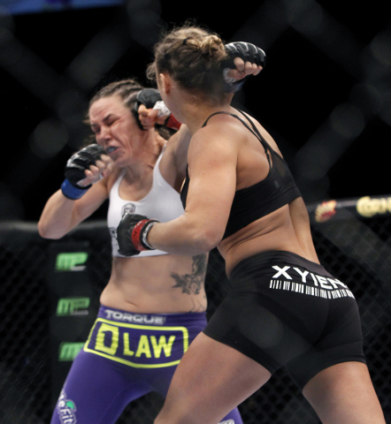 Ronda Rousey, right, hits Alexis Davis during UFC 175 at the Mandalay Bay Events Center in Las Vegas on Saturday, July 5, 2014. (Jason Bean/Las Vegas Review-Journal)