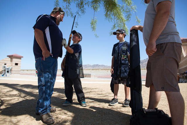 Mark Ellender, left, jokes with his son, Jackson Ellender, 11, second from left, as Carson City Hot Shots' team member Dylan Ziegler, 11, second from right, and Dylan's father, Damon, stand nearby ...