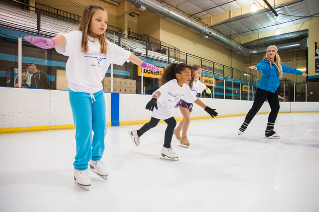 Skating instructor Harley Rhodes, right, teaches, from left, Saylor Hites, 9, Gracie Pendergraft, 8, and Jada Brick, 9, how to ice skate during the Summer Fun on Ice program at the SOBE Ice Arena  ...
