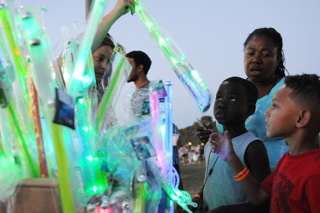 Phyllis Benjamin, second from right, buys her grandchildren Cayden, 5, right, and Nami, 6, light-up swords during the 15th annual Independence Day Jubilee at Craig Ranch Regional Park in North Las ...
