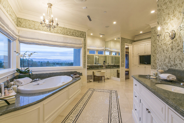Her master bath includes marble floors with inlaid mosaics, a sink area and separate vanity covered in granite. Other amenities include a Thermador towel-warming drawer, bathtub with Bain Ultra Sp ...