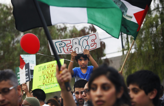 Five -year-old Taha Darovich, middle, holds up a peace sign during a gathering to protest the violence in Gaza in front of the Lloyd George Federal Courthouse in Las Vegas on Saturday, July 19, 20 ...