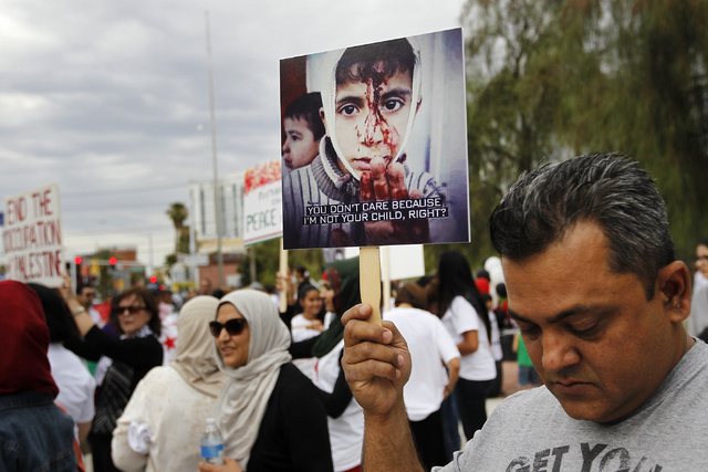 Ahmed Zaman holds a sign during a gathering to protest the violence in Gaza in front of the Lloyd George Federal Courthouse in Las Vegas on Saturday, July 19, 2014. (Jason Bean/Las Vegas Review-Jo ...