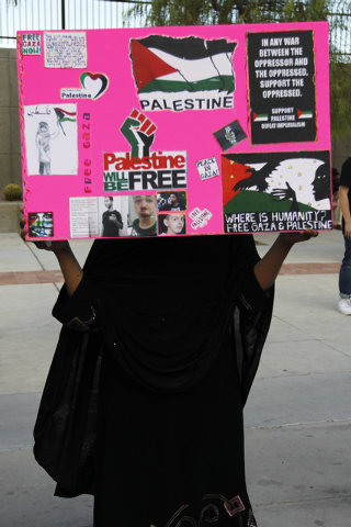 A woman holds up a sign in front of her face during a gathering to protest the violence in Gaza in front of the Lloyd George Federal Courthouse in Las Vegas on Saturday, July 19, 2014. (Jason Bean ...