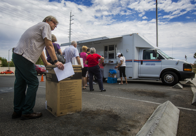 John Kephart stands in line at the United State Postal Service mobile post office  at 455 East Pebble Road, near Bermuda Road on Monday, July 7, 2014. Postal Service is providing mail service outs ...