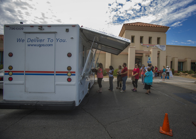 Costumers line up at the United State Postal Service mobile post office in front of the closed post office at 455 East Pebble Road, near Bermuda Road on Monday, July 7, 2014. Postal Service is pro ...