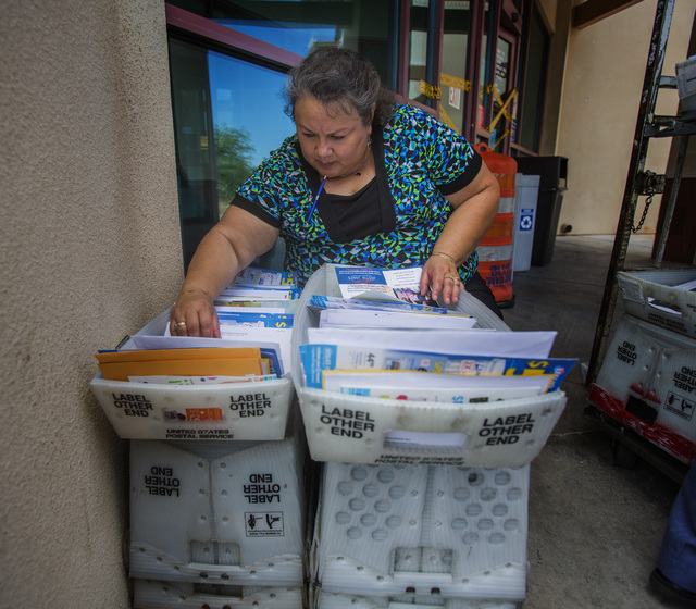 United State Postal Service employee Mayra Castro searches for mail for a customer in front of the closed post office at 455 East Pebble Road, near Bermuda Road on Monday, July 7, 2014. Postal Ser ...