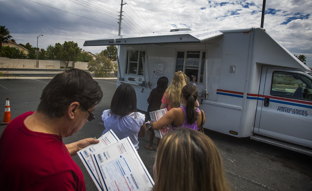 Peter Taitano, left, and his wife Thui Trang Taitano stand in line at the United State Postal Service mobile post office at 455 East Pebble Road, near Bermuda Road on Monday, July 7, 2014. Postal  ...
