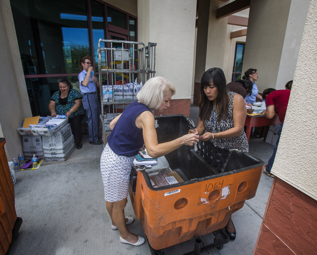Zena Rabang, right, United State Postal Service customer relation coordinator, assists Maria Jones in front of the post office at 455 East Pebble Road, near Bermuda Road on Monday, July 7, 2014. P ...