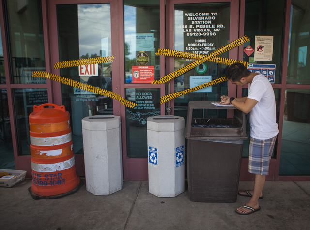 Jonathan Deguzman addresses a letter in front of the closed United State Postal Service post office at 455 East Pebble Road, near Bermuda Road on Monday, July 7, 2014. Postal Service is providing  ...